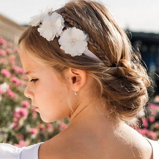 Petite fille portant une couronne de fleurs romantique dans une coiffure tressée