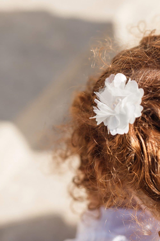 Barrette fleur en tissu sur cheveux roux bouclés