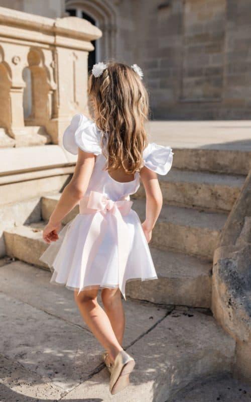 Petite fille coiffée avec deux barrettes fleurs et en tenue de cortège lors d'un mariage
