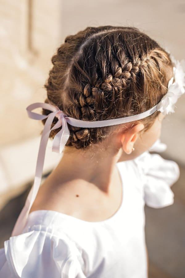 Petite fille avec tresses plaquées et couronne de fleurs en tissu noué avec un ruban rose pâle