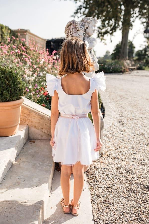 Petite fille avec robe blanche dos nu pour un mariage