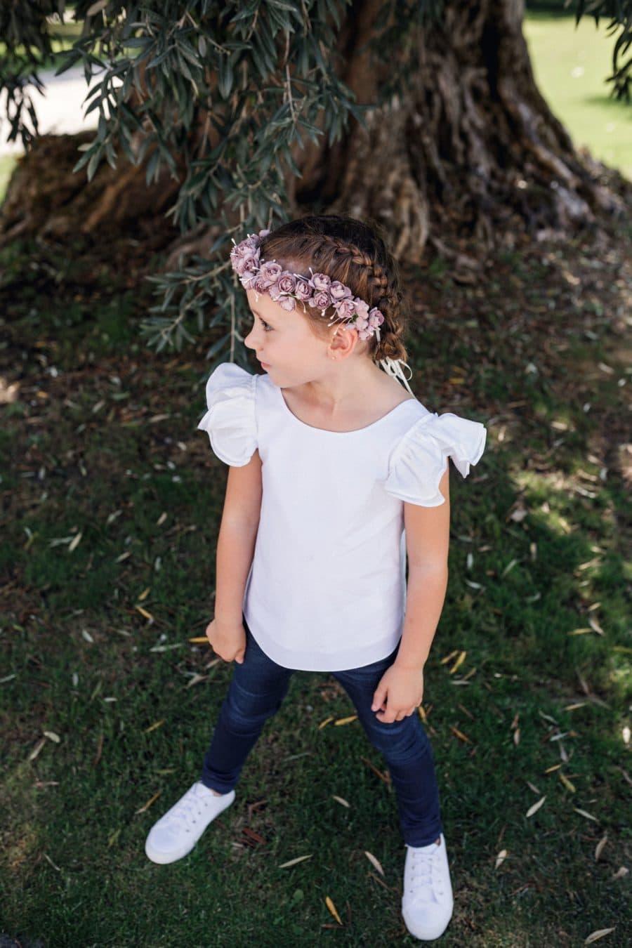 Petite fille avec haut blanc chic pour mariage et jean brut, avec une couronne de fleurs sur le tête