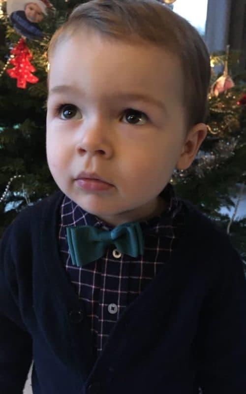 Petit garçon portant un noeud papillon en ruban couleur vert émeraude.
