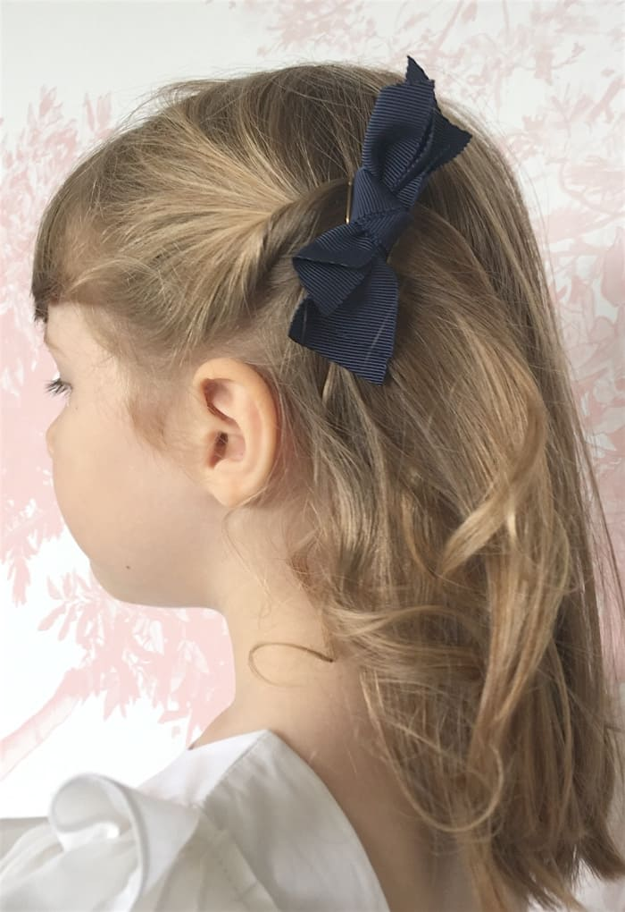 Barrette noeud bleu marine sur cheveux blonds