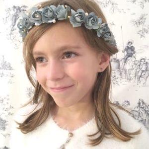 Petite fille portant une couronne de fleurs bleu gris et petits strass
