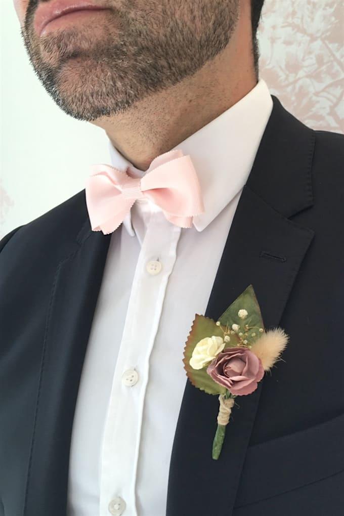 Futur marié avec une boutonnière fleurie sur veste de costume
