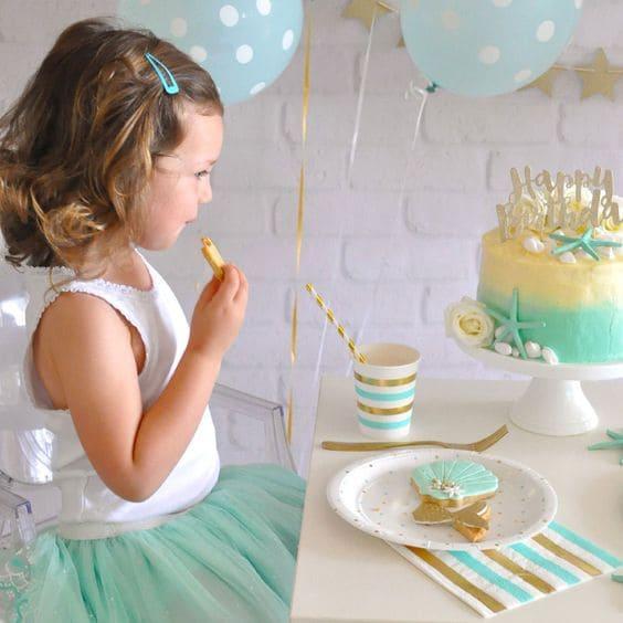 Petite fille à sa fête d'anniversaire avec une décoration vert d'eau